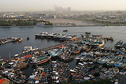 Boats and small ships docked in Dubai creek, with skyline.  Dubai, United Arab Emirates.