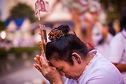 20 OCTOBER 2012 - BANGKOK, THAILAND:  A woman prays while making a cash donation for Buddhist temple's in Thailand's south. More than 2,600 Buddhist Monks from across Bangkok and thousands of devout Thai Buddhists attended the mass alms giving ceremony in Benjasiri Park in Bangkok Saturday morning. The ceremony was to raise food and cash donations for Buddhist temples in Thailand's violence plagued southern provinces. Because of an ongoing long running insurgency by Muslim separatists many Buddhist monks in Pattani, Narathiwat and Yala, Thailand's three Muslim majority provinces, can't leave their temples without military escorts. Monks have been targeted by Muslim extremists because, in the view of the extremists, they represent the Thai state.     PHOTO BY JACK KURTZ