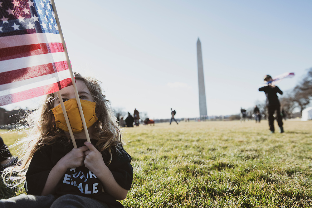 Washington DC, USA - January 21, 2021:  Reise Tuason, 3, and her brother Leo, 6, enjoy a beautiful day on the National Mall the day after the 59th Presidential Inauguration, playing with flags that had been used to decorate the mall for the event. Their family drove from southern California for the inauguration.