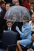 Melania Trump sits with her son Baron Trump under an umbrella during a brief rain at the President Inaugural Ceremony on Capitol Hill January 20, 2017 in Washington, DC. Donald Trump became the 45th President of the United States in the ceremony.
