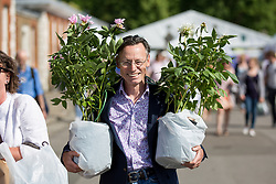© Licensed to London News Pictures. 27/05/2017. London, UK. Members of the public carry exhibitors' plants and flowers from the 2017 Chelsea Flower Show, which ended today (Saturday). A wide variety of unusual and striking display iteams can be purchased on the closing day of The Royal Horticultural Society flagship flower show, helld at the Royal Hospital in Chelsea since 1913. Photo credit : Tom Nicholson/LNP