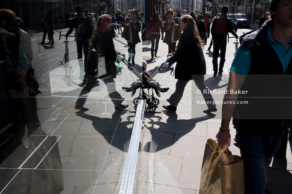 Seen through a polished sheet glass window, a child in its buggy appears as a symmetrical image on a sunny afternoon.