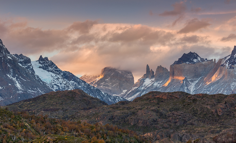 Evening shadows fell over the mountains and the last golden light of the day transformed the clouds into a shroud of mystery. Torres del Paine National Park, Chilean Patagonia.