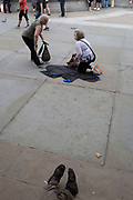 Tired visitors to London struggle to their feet after resting against each other on the pavement in Trafalgar Square, on 15th August 2017, in London, England.