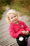 A young girl pauses during a autumn walk on the boardwalk at Bayshore Lake in South Anchorage.