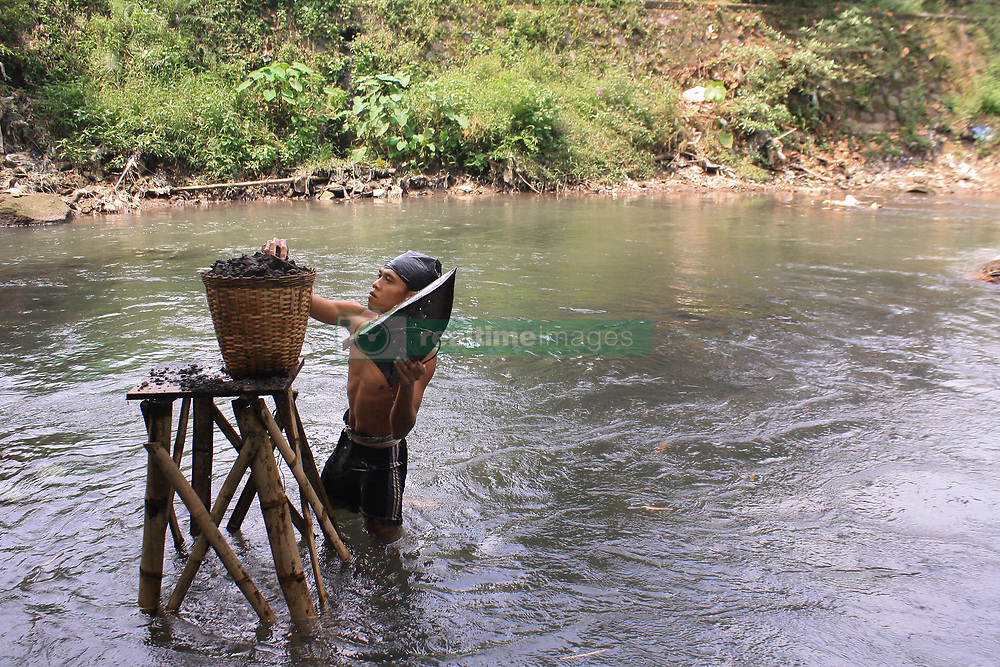 April 28, 2018 - Yogyakarta, Special Region of Yogyakarta, Indonesia - A worker was picking up sand during the traditional mining in the river flowing from upstream  of Mount Merapi. In one day sand will sell for US$ 0,6 or Rp.5000, per bucket made of wood or will be sold to collectors with price of US$15 or Rp.150.000, for a small pickup truk. (Credit Image: © Devi Rahman/Pacific Press via ZUMA Wire)