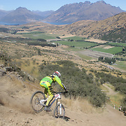 Lawrence Cawte from Rotorua in action during the New Zealand South Island Downhill Cup Mountain Bike series held on The Remarkables face with a stunning backdrop of the Wakatipu Basin. 150 riders took part in the two day event. Queenstown, Otago, New Zealand. 9th January 2012. Photo Tim Clayton