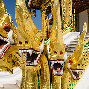Gold nagas guard the entrance to Haw Pha Bang (or Palace Chapel) at the Royal Palace Museum in Luang Prabang, Laos. The chapel sits at the northeastern corner of the grounds. Construction started in 1963.