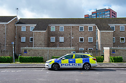 © Licensed to London News Pictures. 25/09/2019. Headington, UK. A police vehicle sits on Bonar Road where police maintained a second scene watch after a murder investigation launched at nearby Foresters Tower visiable in the background. Thames Valley Police were called to Foresters Tower in Wood Farm Road, Headington, at 21:18 BST on 24th September 2019 to reports that a man had fallen from an upper floor of Foresters Tower. The man died at the scene. <br /> Following a search of flats at Foresters Tower, a woman was located on the fourth floor with severe neck injuries and was pronounced dead at the scene.. Photo credit: Peter Manning/LNP