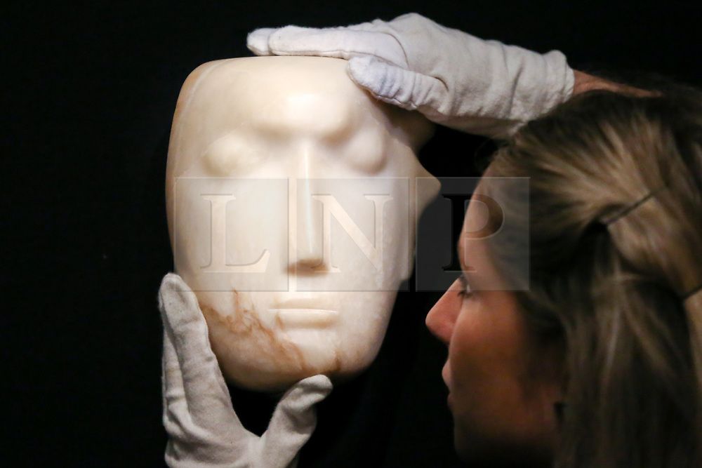 """© Licensed to London News Pictures. 12/11/2018. London, UK. A staff member holds """"The Man Behind the Mask"""", a Henry Moore'smasterpiece (British, 1898-1986). (Estimate: £1,000,000-1,500,000). The work is one of 12 known, small carvings by Moore titled Mask, and, uniquely, is the only one carved from alabaster.<br /> Bonhams Modern British and Irish Art photocall. Auction to be held on 14 November 2018. Photo credit: Dinendra Haria/LNP"""