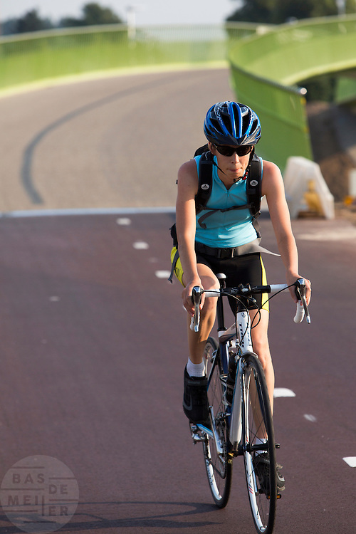 Bij Lent rijdt een meisje op de racefiets over 't Groentje, de nieuwe fietsbrug die onderdeel is van het Rijn-Waalpad, de snelfietsroute tussen Arnhem en Nijmegen. Als de route helemaal klaar is, kunnen fietsers binnen 40 minuten van Arnhem naar Nijmegen fietsen. De snelfietsroute kent weinig obstakels en moet het aantrekkelijk maken om ook langere afstanden met de fiets af te leggen.<br /> <br /> Cyclists ride on 't Groentje (the little green), the new bike bridge which is part of the Rijn-Waalpad, the fast cycling route between Arnhem and Nijmegen. When the route is finished, cyclists can get within 40 minutes from Arnhem to Nijmegen. The fast cycle route has few obstacles and to make it attractive to commute long distances by bicycle.