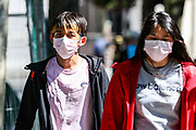 People wearing face surgical masks as they walk in central London on Wednesday, June 24, 2020. Secretary of State for Transport Grant Shapps, announced that all passengers must wear face masks on public transport starting from 15 June and warned that wearing of a facemask would be a condition to travel and failure to comply will result to failure to travel or being fined. (Photo/ Vudi Xhymshiti)
