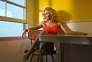 Actor and singer Lisa Robert photographed in Hollywood California.  She wears a salmon colored slip as she perches herself at her table against a half yellow wall, looking toward her window.