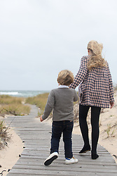 little girl and boy walking on a beach walkway towards the ocean in the Winter