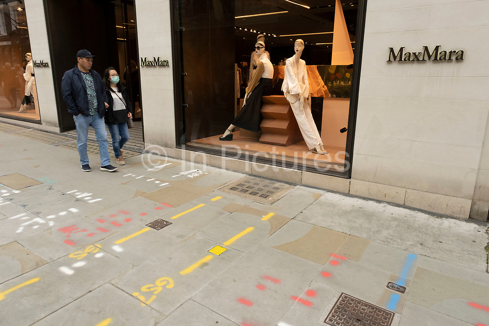 People pass the Max Mara store wearing face masks on Bond Street on 25th May 2021 in London, United Kingdom. These high end brands are seen next to each other on a very ordinary wall. Bond Street is one of the principal streets in the West End shopping district and is very upmarket. It has been a fashionable shopping street since the 18th century. The rich and wealthy shop here mostly for high end fashion and jewellery.