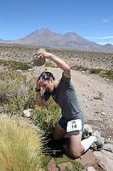 © Licensed to London News Pictures. 14/11/2013.<br /> <br /> 2nd place Basti Haag (GER) cools off.<br /> <br /> Inaugural Volcano Marathon, Atacama Desert, Chile. The race took place in the Atacama Desert in Chile, beginning at an altitude of 4,400 metres (14,500 feet) in the vicinity of Lascar Volcano. It was a gruelling affair for many of the competitors who had to encounter some challenging hills and manage the impact of the heat and oxygen deprivation. The average altitude of the entire race was close to 4,000 metres and temperatures reached the mid 20s Celsius, or almost 80 Degrees Farenheit.<br /> <br /> Photo credit : Mike King/LNP<br /> <br /> Further information and link to video here: https://www.dropbox.com/s/0277bepxvo0t8il/Marathon%20copy.txt