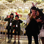 Korean visitors to Lotte world pose for photographs with their friends during night time festivities. Lotte World is the world's largest indoor theme park which includes shopping malls, a luxury hotel, and an Ice rink. Opened on July 12, 1989, Lotte World receives over 8 million visitors each year. Seoul, South Korea. 21st March 2012. Photo Tim Clayton