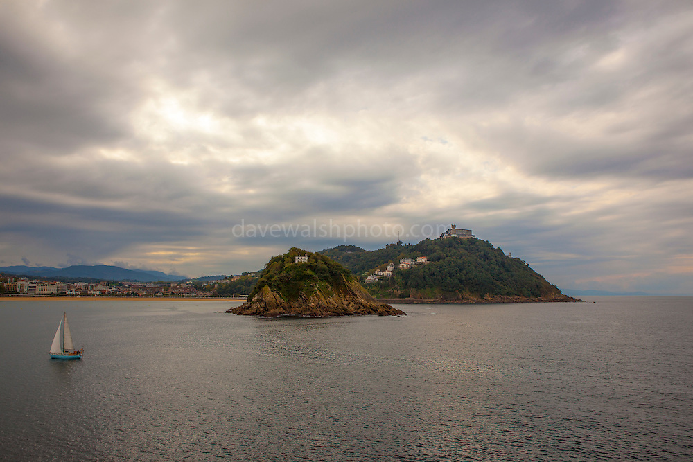Yacht sails by the Isla de Santa Clara, Bahia de la Concha, San Sebastian Donostia, Euskadi, Spain
