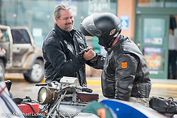 Scott Byrd of Arkansas greets Ryan Allen at a rainy gas stop during the Motorcycle Cannonball Race of the Century. Stage-11 ride from Durango, CO to Page, AZ. USA. Wednesday September 21, 2016. Photography ©2016 Michael Lichter.
