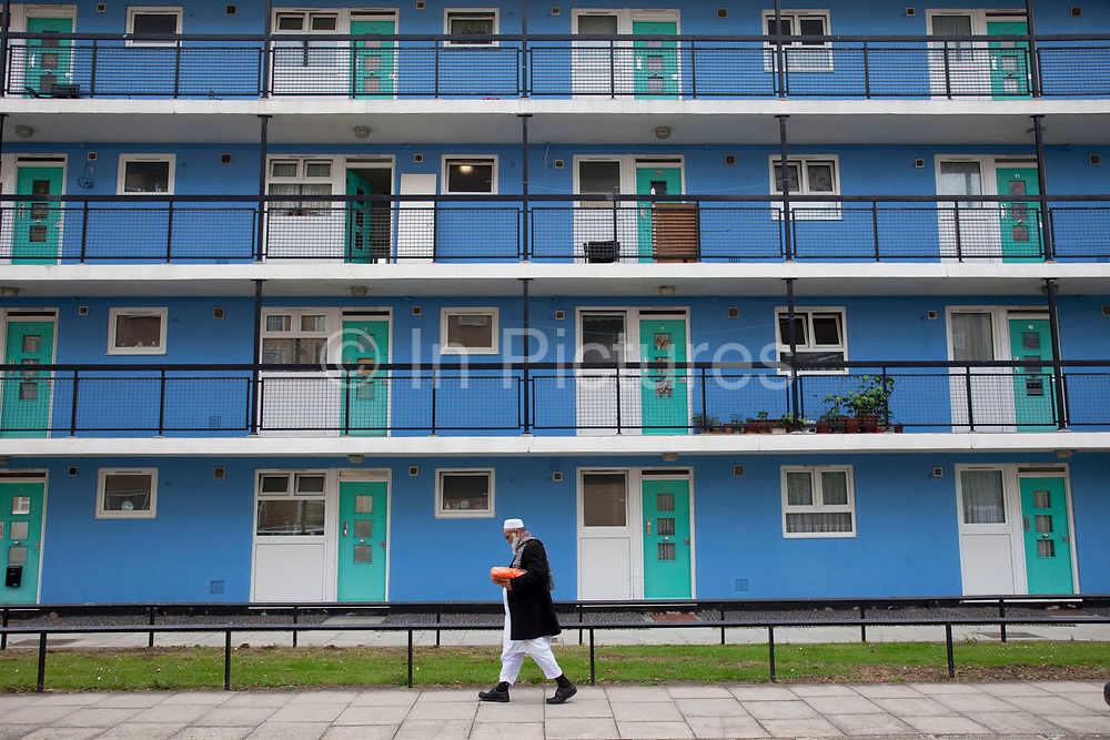 Muslim man near to council flats in Tower Hamlets, East London. Many people are at risk of losing their homes in London with the introduction of new benefit rules, which may push many people renting or who own council apartments out of the city. Tower Hamlets is a poor and over populated borough with many people living in small homes in high rise apartment blocks.