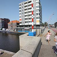 Nederland, Zaandam , 5 juli 2013.<br /> Wandeling door de binnenstad van Zaandam.<br /> Starten bij De Werf aan de Oostzijde. Daarvandaan kun je lopen op een soort boulevard tussen de flats en het water. De eerste stop is De Fabriek, filmhuis en eetcafé met terras aan de Zaan met uitzicht op de sluis. Daarna de sluis zelf.<br /> Dan langs het winkelgebied richting de Koekfabriek: Het oude Verkade pand dat is verbouwd en waar nu de bieb en sportschool en restaurant etc. in zitten.<br /> (Dat is aan de overkant van het startpunt) en misschien nog de Zwaardemaker meepakken aan de Oostzijde. Dat is een oud pakhuis die Rochdale enige jaren geleden heeft verbouwt tot appartementen met een stukje Nieuwbouw.<br /> Ook doen: het Russische buurtje vlakbij de Zaan. Dit jaar staat Rusland in de schijnwerpers en Zaandam heeft een speciale band met Rusland, vanwege het Czaar Peterhuisje en de Russische buurt. <br /> Op de foto: 1 van de bruggen die Oostzijde met Westzijde verbindt. Links aan de Zaan de wandelboulevard met de panden De Steven, de Werf, De Helling en de Kiel.<br /> Foto:Jean-Pierre Jans