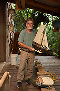 Senior man holding a boat in his workshop