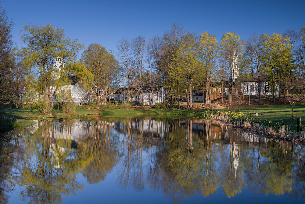 Homes and churches and early spring trees, reflections in pond, Center Sandwich, NH