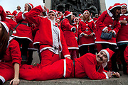 London, UK. Sunday 9th December 2012. A flash mob of Santas descends on Trafalgar Square. One decided to simulate sex with another, it's a bawdy buy fun and good natured atmosphere. Christmas celebrated here with the annual Santa Pub Crawl party visiting the famous pubs & sights of London with everyone decked out in jolly red Santa suits. Organised by Fanatics, an Australian sports and party company.