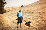 Older man walking dog in field