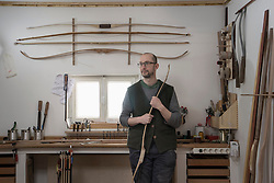 Male bow maker holding bow and thinking in workshop, Bavaria, Germany