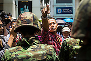 """25 MAY 2014 - BANGKOK, THAILAND: A Thai """"Red Shirt"""" supporter of the ousted civilian government confronts soldiers at a demonstration against the military junta. Public opposition to the military coup in Thailand grew Sunday with thousands of protestors gathering at locations throughout Bangkok to call for a return of civilian rule and end to the military junta.     PHOTO BY JACK KURTZ"""