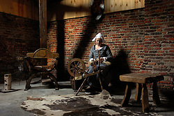 AARSCHOT, BELGIUM - Maris Lowers works at a spinning wheel in the Sint-Rochustoren Tower, a medieval tower that was closed to the public for 600 years. Lowers is a member of the Orde Van De Hagelanders, a group who recreates medieval life and convinced the city of Aarschot to allow them to restore the tower to its medieval glory. (Photo © Jock Fistick)
