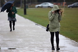 © Licensed to London News Pictures. 27/09/2021. London, UK. A woman holds onto her hood to shield herself from wet and and windy weather on Blackheath Common in South East London. Rain showers are forecasted to continue in parts of London and South East England for the rest of the week.  Photo credit: George Cracknell Wright/LNP