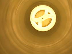 A compact fluorescent (CFL) light bulb with a color temperature (Kelvin) of approximately  3200 inside a metal lampshade.