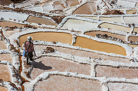 Maras, Peru - July 23, 2013: woman at Maras salt mines in the peruvian Andes at Cuzco Peru on july 23, 2013