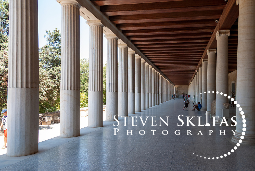 Ancient Agora. Athens. Greece. View of the long pillared lower floor of the Stoa of Attalos, a beautifully restored colonnaded building in the Agora. Constructed by King Attalos II of Pergamon between years 159 – 138 BC, it is thought to be used as offices and shops and administrative centre.  It is a two-storeyed building with Doric columns fronting the ground floor exterior with Ionic columns splitting the interior long pillared hall into two aisles. The upper floor is fronted by Ionic columns. The building was faithfully reconstructed in 1953-56 and is used a museum to house finds form the Agora site.