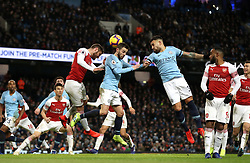 Manchester City's Bernardo Silva (centre) and Arsenal's Shkodran Mustafi (left) compete for a header during the Premier League match at the Etihad Stadium, Manchester.