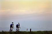 Nederland, Nijmegen, 4-5-2005..Twee wielrenners fietsen op de dijk bij ondergaande zon. Zonsondergang. Wielersport, recreatie, natuur, ruimte, sport, ontspanning, afleiding...Foto: Flip Franssen/Hollandse Hoogte