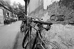 Bicycles leaning on old wall in a Beijing hutong