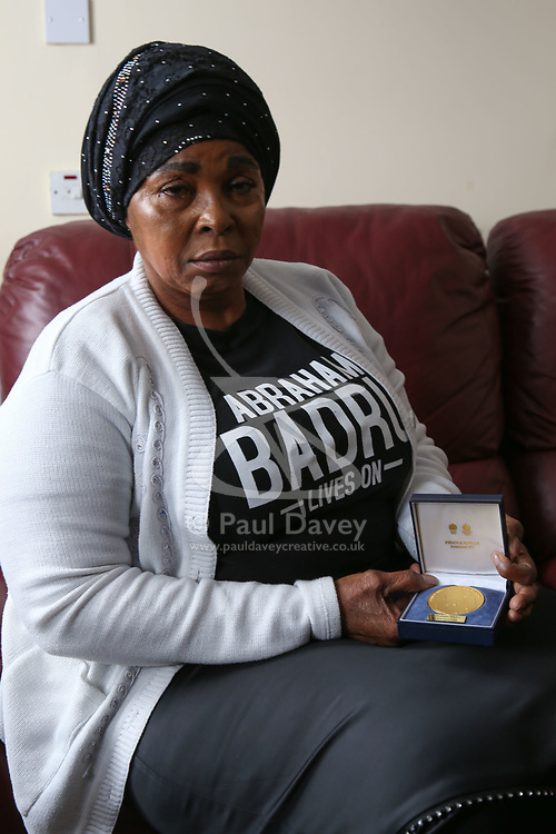 Ronke Badru, mother of Abraham Badru holds the National Police Bravery Award medal her son Abraham received. Abraham Badru, a personal trainer, 26, was shot in the chest on 25th March in Ferncliff Road, E8. He received a National Police Bravery Award after intervening in a rape and giving evidence in court. London, April 25 2018.