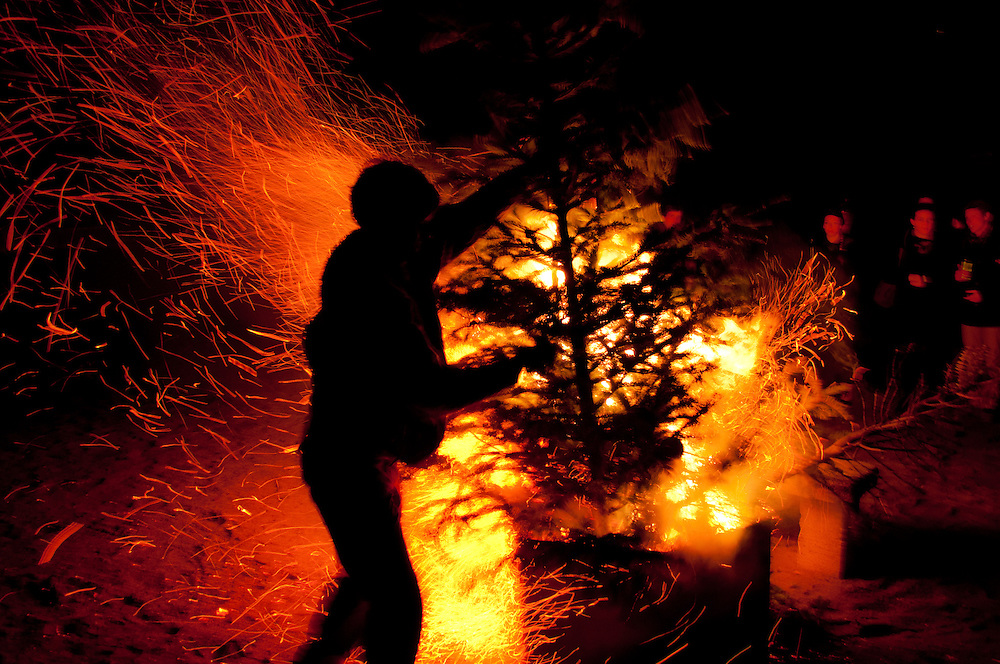 A photo of a man putting a Christmas tree in a burn pit.