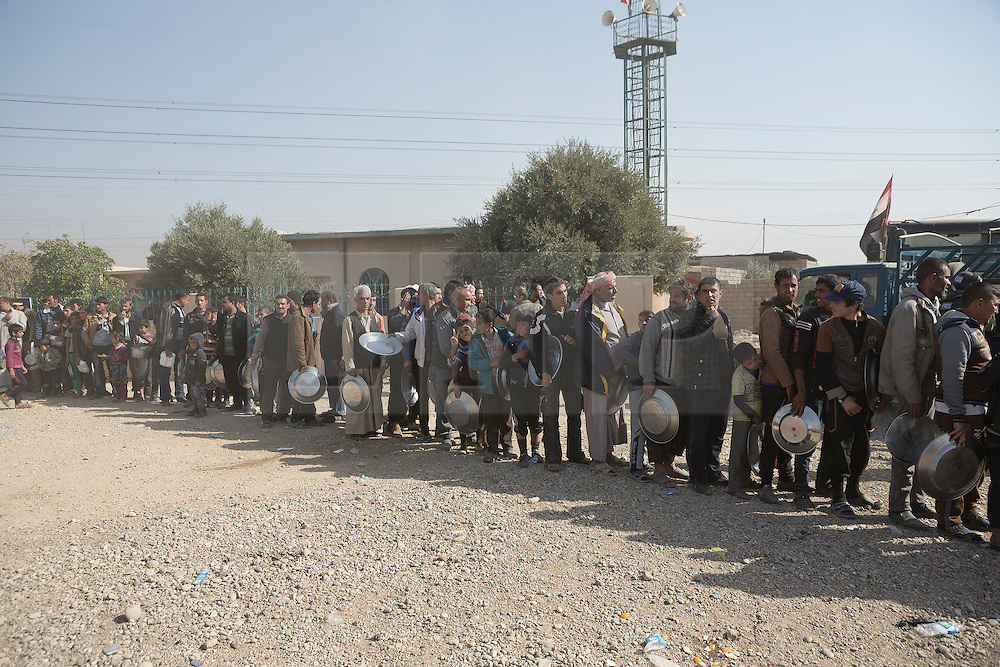 Licensed to London News Pictures. 11/11/2016. Mosul, Iraq. Iraqi refugees, who have escaped fighting in Mosul, queue for lunch outside a mosque, where many are temporarily staying, in the city's Hay Intisar district on the south east of the city. The district was taken by Iraqi Security Forces (ISF) around a week ago and, despite its proximity to ongoing fighting between ISF and ISIS militants, many residents still live in the settlement.<br /> <br /> The battle to retake Mosul, which fell June 2014, started on the 16th of October 2016 with Iraqi Security Forces eventually reaching the city on the 1st of November. Since then elements of the Iraq Army and Police have succeeded in pushing into the city and retaking several neighbourhoods allowing civilians living there to be evacuated - though many more remain trapped within Mosul.  Photo credit: Matt Cetti-Roberts/LNP