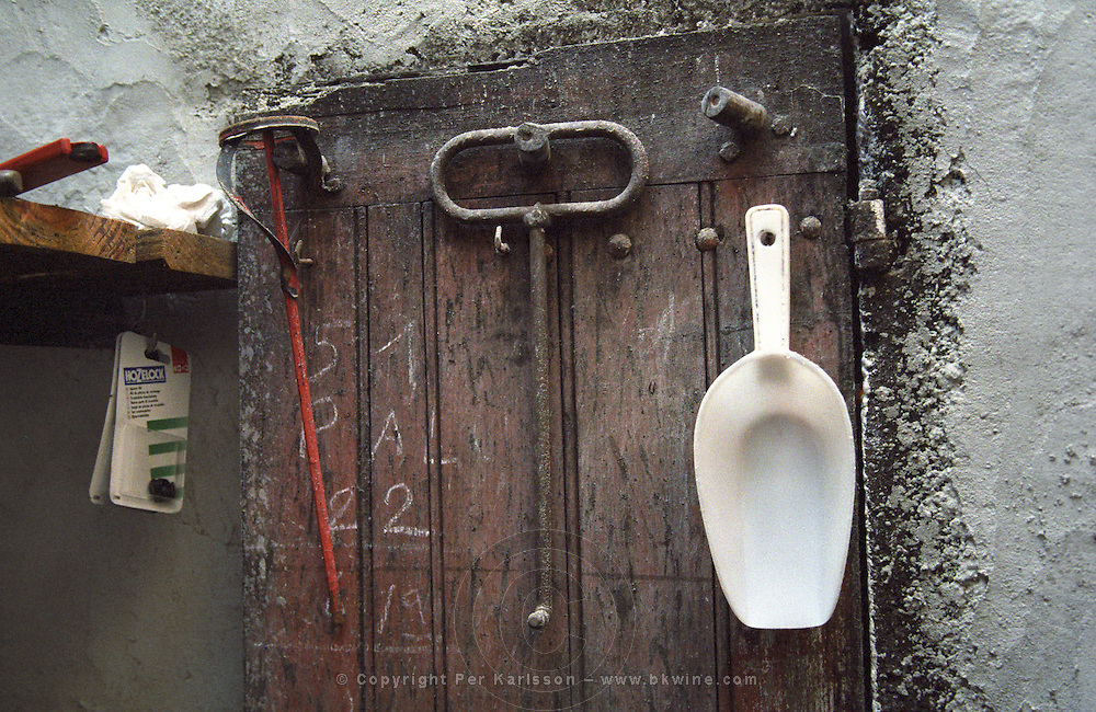 Tools in the winery hanging on a tool board: a stirrer, a hook, a plastic spoon against a white wall  Chateau Caillou, Grand Cru Classe, Barsac, Sauternes, Bordeaux, Aquitaine, Gironde, France, Europe