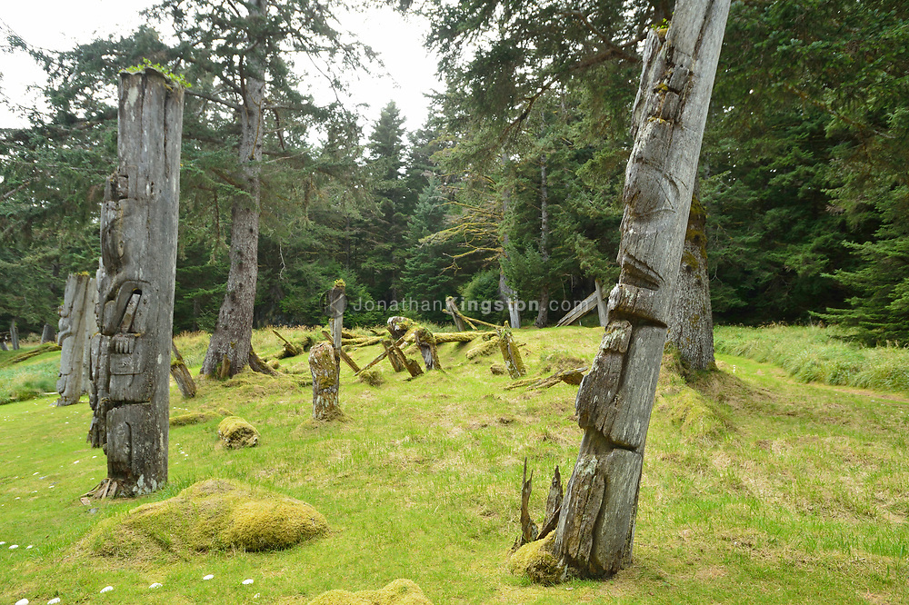 Mortuary poles, the grave of a high status person, carved with the crest of the deceased at UNESCO world heritage site, SGang Gwaay Llnagaay, Haida Gwaii, British Columbia.  A cavity at the top of the pole is where the remains of the deceased were placed.