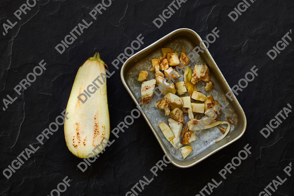 Half aubergine in dices placed in a metal tray with flatlay look dark theme
