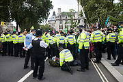 Metropolitan Police officers prepare to arrest a climate activist from Extinction Rebellion who had occupied a road around Parliament Square during a Back The Bill rally on 1st September 2020 in London, United Kingdom. Extinction Rebellion activists are attending a series of September Rebellion protests around the UK to call on politicians to back the Climate and Ecological Emergency Bill (CEE Bill) which requires, among other measures, a serious plan to deal with the UK's share of emissions and to halt critical rises in global temperatures and for ordinary people to be involved in future environmental planning by means of a Citizens' Assembly.