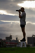 A man stands on a collapsable stool to photograph military aircraft at NAF Atsugi airbase near Yamato, Kanagawa, Japan. Thursday September 10th 2020