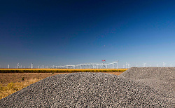 Rural field with wind farm turbines on the horizon and mounds of gravel in the foreground.