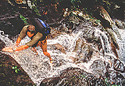 Shannon Walsh climbs through a waterfall while exploring the tropical rain forest of Tioman Island in Malaysia.