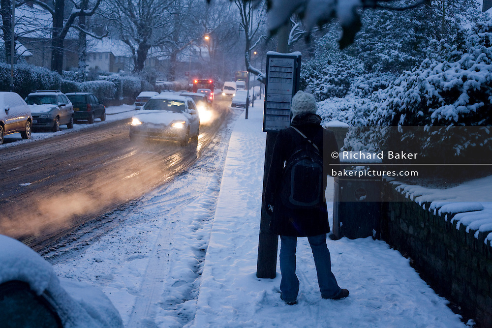 As blue dawn light brightens to become another wintry day in south London  a commuter awaits the arrival of a distant red bus to climb a slippery hill. Standing by the timetable of the bus stop on Red Post Hill  in the borough of Southwark  traffic approaches slowly on a road that controversially  appears not to have been gritted properly for vehicles to maintain a proper grip on this snowy surface. Headlights point uphill and the freshly-fallen snow has started to freeze so wheel and tyre traction will prove ever-difficult for those trying to journey to work.